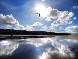 Kitesurfing under a winter sun at Gwithian Towans beach kernow